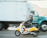 Woman driving a vespa, with blurred background