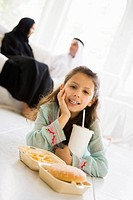 Young girl with fast food in living room smiling with parents in background high key/selective focus