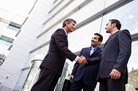 Three businessmen standing outdoors by building shaking hands and smiling high key/selective focus