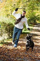 Man outdoors with dog on path in park holding branch smiling selective focus