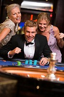 Three people in casino playing roulette smiling selective focus