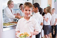 Students in cafeteria line with one holding his healthy meal and looking at camera depth of field
