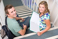Two students sitting on staircase with notebooks selective focus