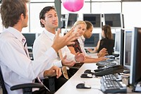 Five businesspeople in office space with a ball being thrown