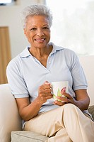 Woman sitting in living room with coffee smiling
