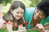 Mature woman and a girl lying on grass and listening to an MP3 player