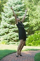 Side profile of a mature woman cheering with her arm outstretched in a park