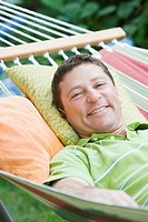 Portrait of a mature man lying on a hammock and smiling
