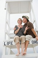 Low angle view of a mature couple sitting in a lifeguard hut