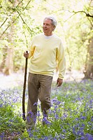 Man walking outdoors with walking stick smiling