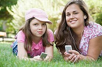 Portrait of a young woman and a girl lying on grass in a park and listening to MP3 players
