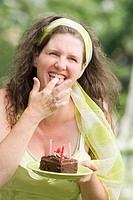 Mature woman tasting a birthday cake