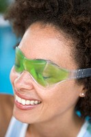 Woman sitting poolside using eye mask smiling
