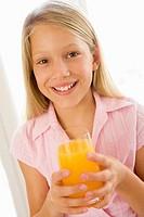 Young girl indoors drinking orange juice smiling
