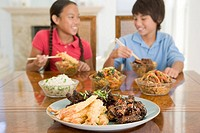 Two young children eating chinese food in dining room smiling