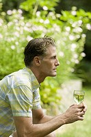 Side profile of a mature man holding a glass of wine and thinking