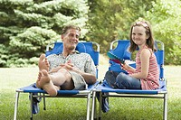 Mature man reclining on a lounge chair beside his daughter