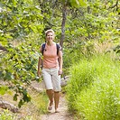 Mature woman walking in a forest and smiling