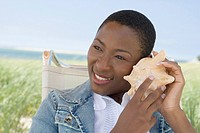 Close_up of a mid adult woman listening to a conch shell and smiling