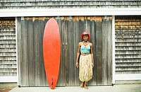 Portrait of a mid adult woman standing beside a surfboard and smiling