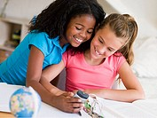 Young Girls Distracted From Their Homework, Playing With A Cellphone