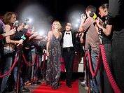 Couple walking down red carpet photographed by paparazzi