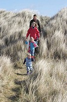 Parents with two children 3_6 walking in long grass