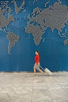 Woman with suitcase walking past world map on wall