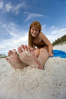 Barefoot girl sitting on beach, smiling, portrait