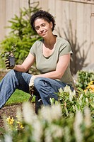 Mid adult woman holding plant in garden, portrait