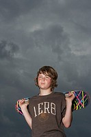Teenage boy 13_15 holding skateboard standing against sky low angle view