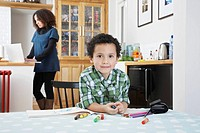 Portrait of boy 5_6 sitting at table mother using laptop in background