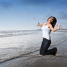 Side profile of a young woman jumping with her arms outstretched on the beach