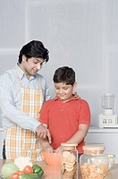 Young man helping his son in preparing food