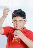 Close_up of a boy holding a conical flask and a pipette
