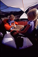 Two sisters and their puppy playing a game of checkers while camping on Mount Judah CA