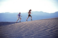 Two women running on a sand dune in Death Valley CA