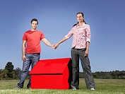 Couple holding hands over small model house