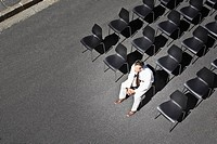 Businessman sitting on office chair in roadway (thumbnail)