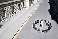 Businessman standing in circle of office chairs in roadway