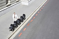 Businessman with office chairs on sidewalk