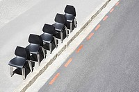 Line of office chairs on sidewalk