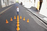 Man standing with arrow_shaped traffic cones in roadway