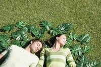 Couple laying on grass surrounded by green leaves (thumbnail)