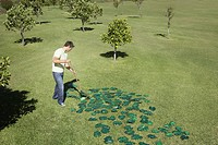 Man raking pile of green leaves in field