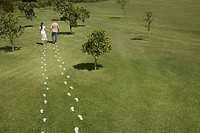 Couple walking through field trailing footprints