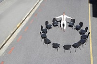 Businessman sitting in circle of office chairs in roadway