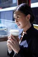 Young Businesswoman Riding Tram, Holding Coffee Cup, Looking Away, Smiling