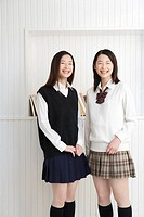 Portrait of twin sisters in school uniform, smiling and looking at camera, front view