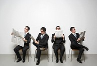 Businessmen reading newspaper